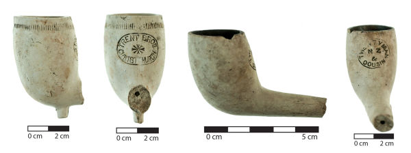 Two clay pipes marked with the names of local Christchurch retailers. Image: J. Garland.